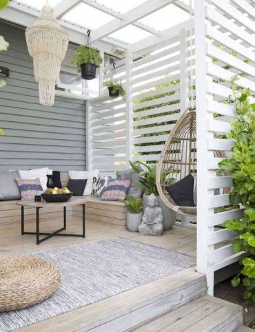 A-boho-and-zen-deck-with-a-built-in-bench-a-rattan-hanging-chair-a-bead-chandelier-a-coffee-table-and-a-jute-ottoman
