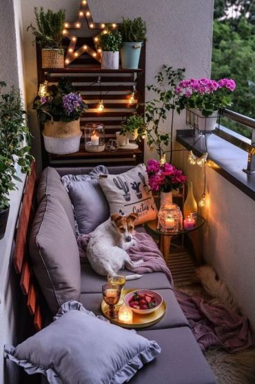 A-cozy-small-balcony-with-a-pallet-wall-and-sofa-some-potted-blooms-and-greenery-and-candle-lanterns