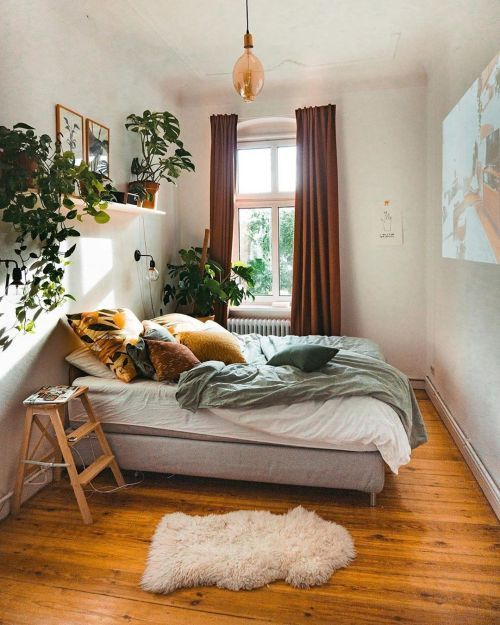 A-small-cozy-bedroom-with-an-upholstered-bed-jewel-tone-textiles-potted-greenery-and-faux-fur-plus-a-pendant-lamps
