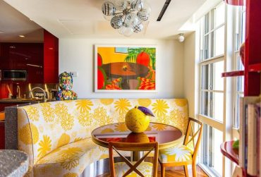 Yellow-banquet-style-seating-steals-the-show-in-this-tropical-style-dining-room-768x512