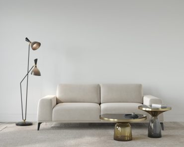 Living room in beige color, with a soft sofa, stylish floor lamp and glass tables