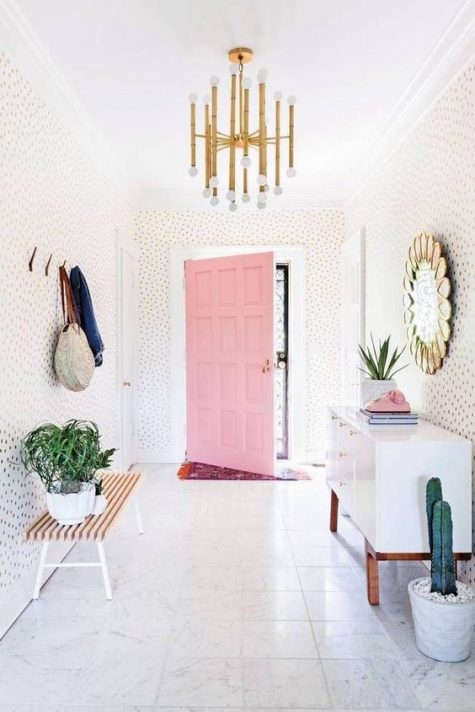 A-modern-playful-and-whimsical-entryway-with-polka-dot-walls-a-white-sideboard-a-bench-clothes-racks-and-a-mirror