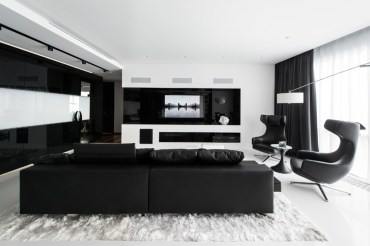 Black-and-white-living-room-ideas-large-wall-cut-outs-black-leather-couch-textured-rug-tinted-indoor-windows