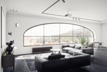 Black-living-room-furniture-2-large-shaped-window-black-leather-couches-geometric-decor-large-mirror-study-area-indoor-plants-wooden-floor