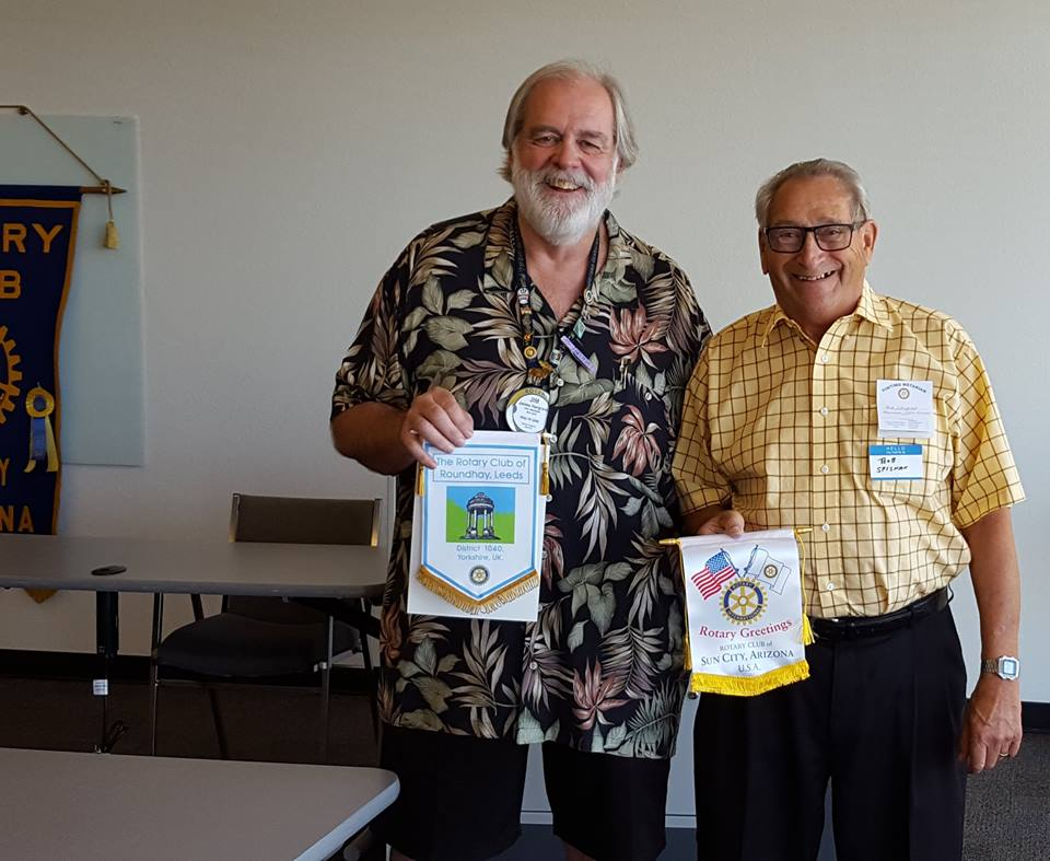 Bob Spishak exchanges banners with the president  Dean Pokrandt of Sun City Rotary Club AZ