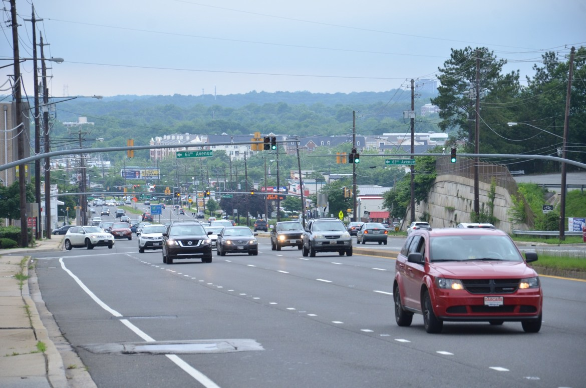 Cars drive along a moderately-congested Greenbelt Road, a six-lane suburban throughway overlooking a green horizon.