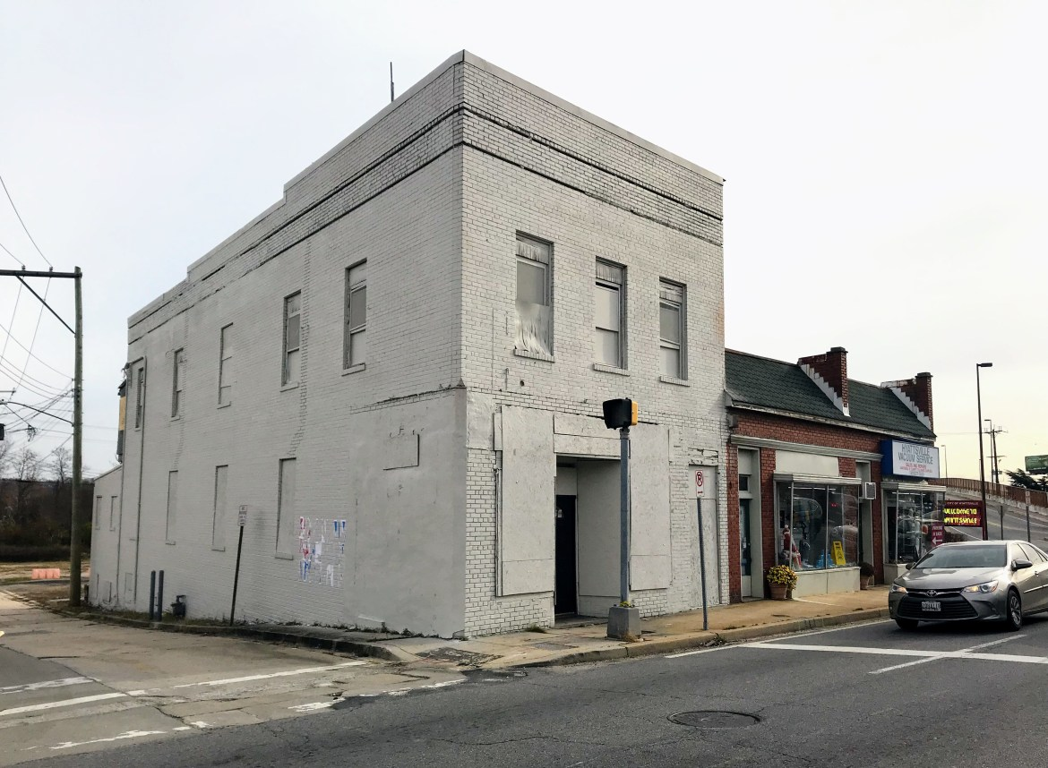 A two-story greyish brick building stands on a corner lot in an older suburban streetscape. It adjoins a red single-story building that houses a retail storefront with a sign reading Hyattsville Vacuum Service. The sidewalk is cracked narrow, receding left to right into the distance. It is and stained from years of brick erosion. Infront of the buildings, at the corner crosswalk, is a crosswalk sign.