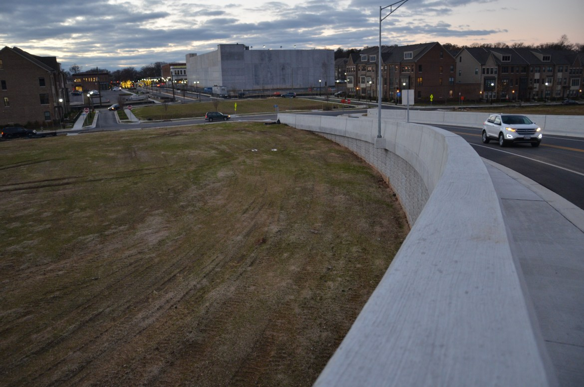 A partly-cloudy winter sky hovers over Riverdale Park Station at dusk, seen looking west from the Van Buren Street overpass. In the foreground, the concrete bridge platform curves away from the viewer, leading the eye to an unadorned concrete structure in the center of the photograph. This is the parking garage. It is flanked by rows of townhomes. A white sports utility vehicle is seen on the bridge, driving eastbound.