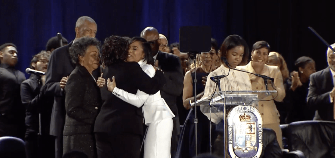 Angela Alsobrooks, clad in white, hugs a member of her family after taking the oath of office for Prince George's County Executive Dec. 3, 2018. She is the first woman to lead Prince George's County.