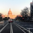 The U.S. Capitol Building is bathed in orange light, seen from the center of Pennsylvania Avenue's bike lanes.