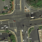 An overhead-view of a large, suburban intersection. Crosswalks exist on three of the four sides of the intersection.