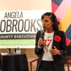 "An African-American woman, Angela Alsobrooks, stands holding a microphone infront of a sign reading ""Angela Alsobrooks for County Executive."""