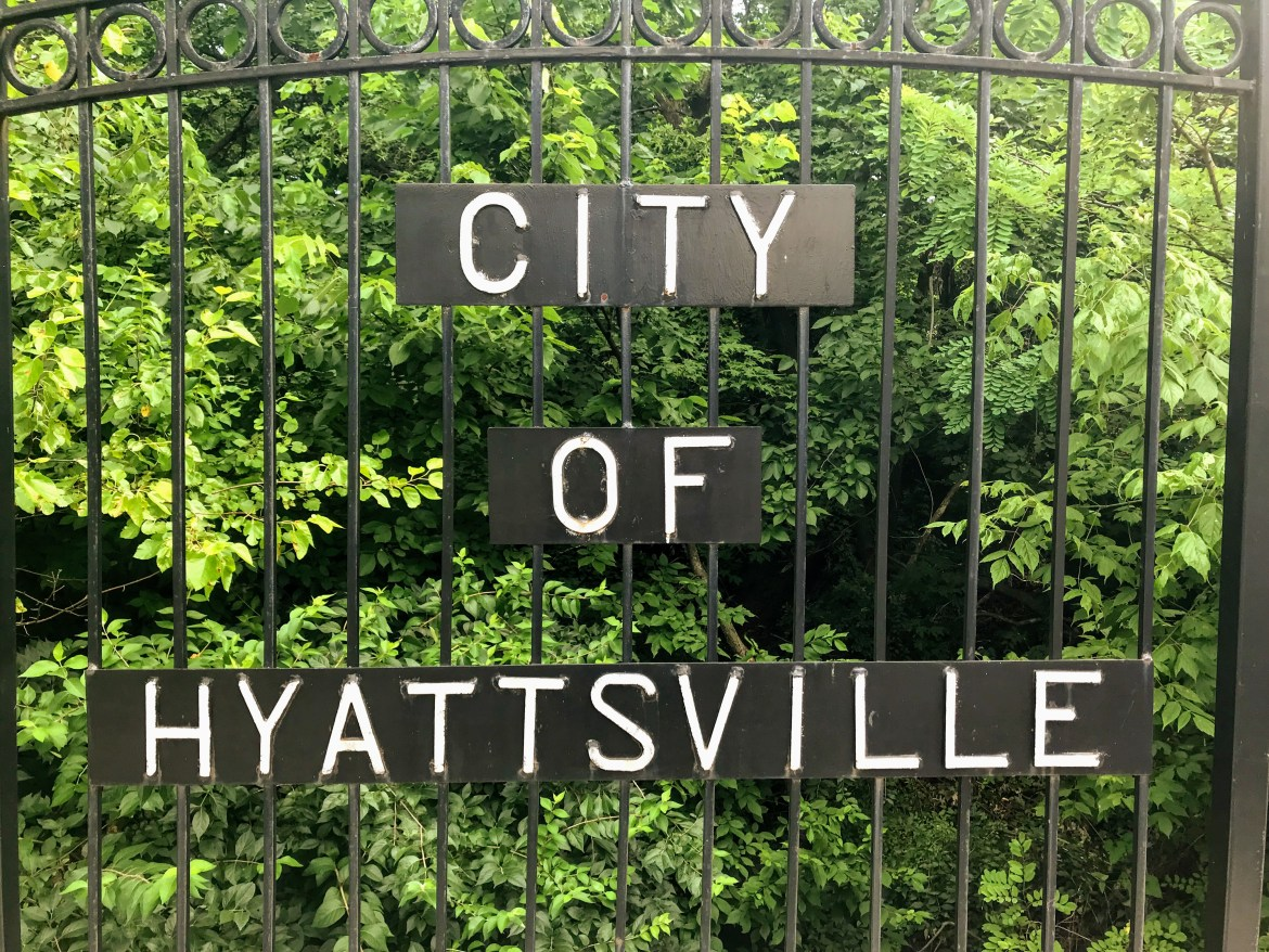 "A black metal gate bears a three-panel sign reading, top to bottom, ""City of Hyattsville."" In the background, bright green leaves."