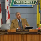 "A middle-aged African American man, wearing a brown jacket with a grey sweater and blue shirt, sits at a wood-paneled dais, gesturing as he speaks. Above and behind him, a sign reads ""Greenbelt."" Infront of him, a placard reads ""Emmet V. Jordan, Mayor"" To the left of him sits a younger African-American man wearing a dark shirt, infront of a placard reading ""Colin A. Byrd, Councilmember"". To the right, an older white woman sits, wearing a matching red blazer and necklace, her nameplate reads ""Judith F. Davis, Mayor Pro-Tem."""