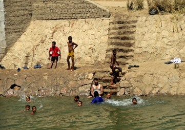 Kids taking a bath in a canal