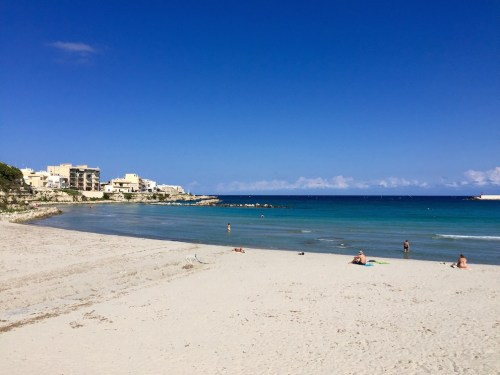 A couple people enjoying Otranto's beach