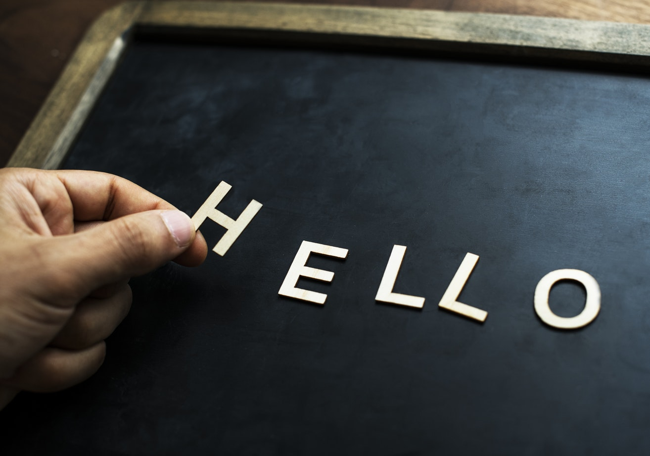 photograph of a blackboard where the word 'hello' is being spelled out in white magnetic letters by a persons hand placing them on the board
