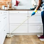 a photograph of a woman cleaning a kitchen floor with a mop. she is wearing blue jeans and a checked shirt.
