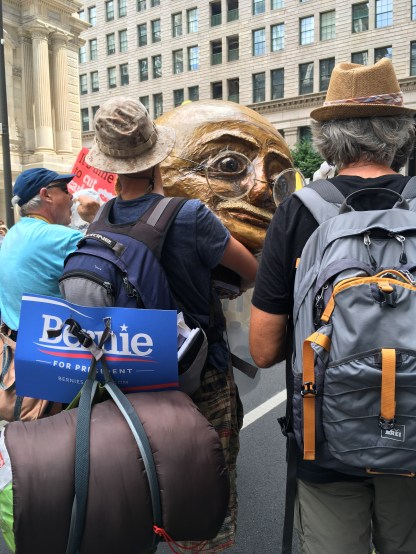 A protester holds the prop head of Mahatma Ghandi while waiting for the march to begin.