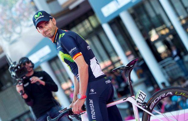 Alejandro Valverde podczas Giro d'Italia. Hiszpan stoi przy rowerze i ogląda się na kolegów z ekipy.