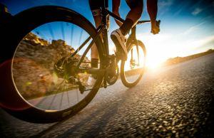 kolarz na podjeździe ku wschodzącemu słońcu