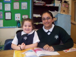 Reading buddies - an older student helping a younger students read