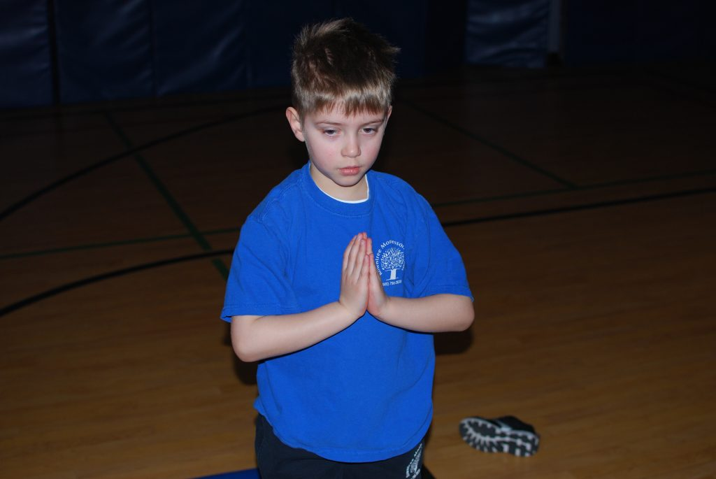 A focused student demonstrating prayer pose