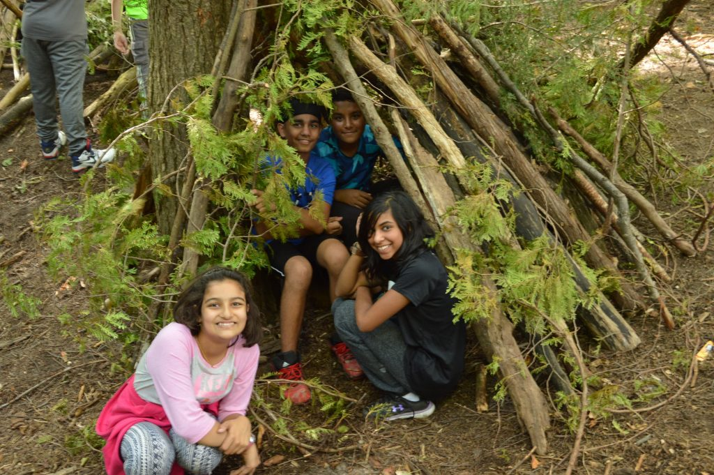Using teamwork skills to build a shelter in the woods