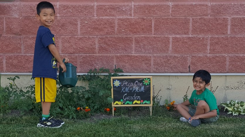 Kindergarten Montessori students watering garden at RMS Academy campus