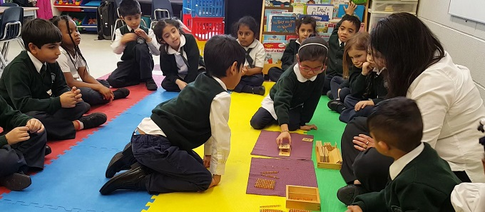 Students in Prep-ONE (Senior Kindergarten) at Rowntree Montessori Schools in Brampton sitting in a circle learning how to count using counting materials