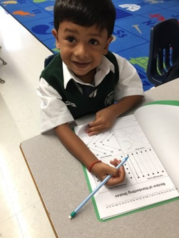 Kindergarten student learning to read using worksheets
