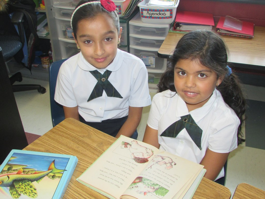 Older students teaching a younger student how to read at Rowntree Montessori Schools in Brampton.