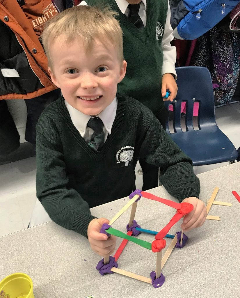 A male PrepOne (SK) student using popsicle sticks to build cubes