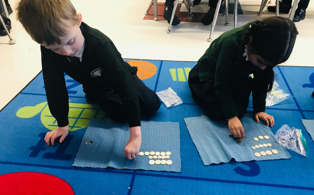 Two students counting coins during a math lesson in Senior Kindergarten