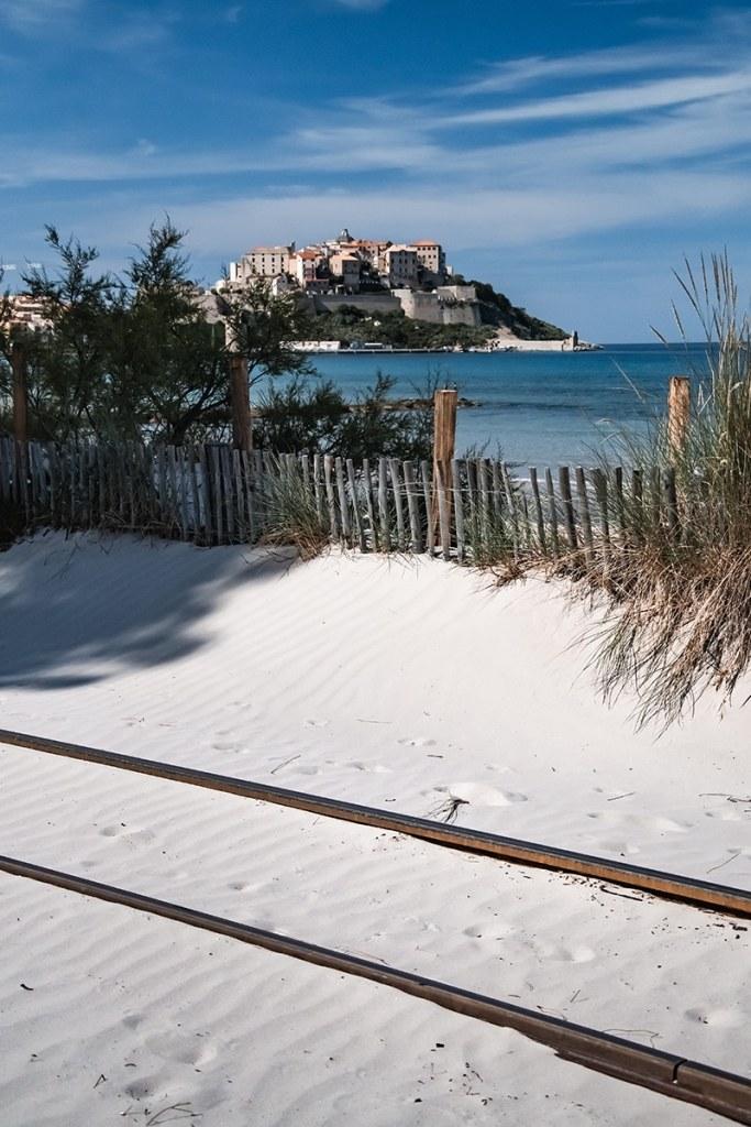 Voies ferrées dans le sable devant la citadelle à Calvi
