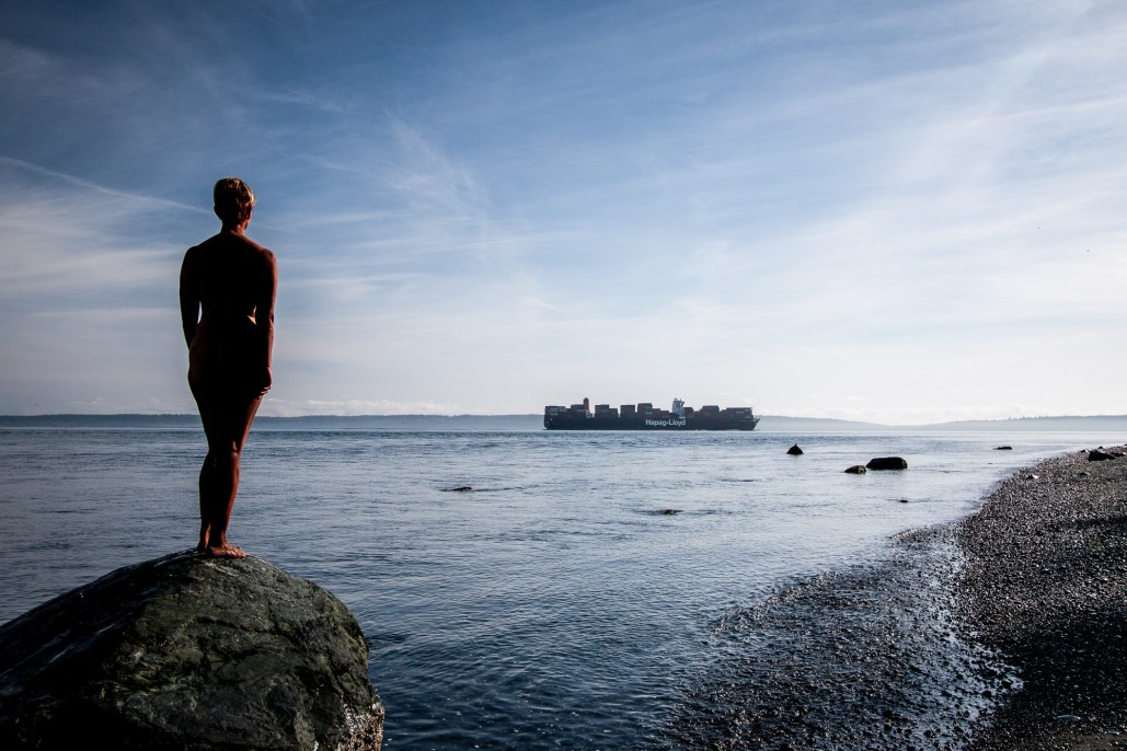 photo of a nude woman on a rock watching a container ship pass by