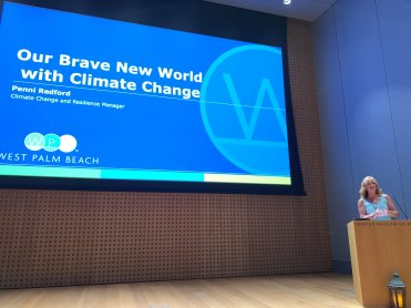 Penni Redford at the podium at the Norton museum of art speaking on climate change