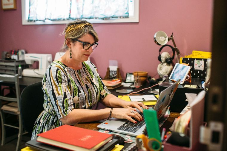 Roxy Hotten Celebrant writing her blog posts at her desk in her home office.