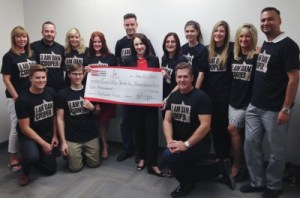 Dan Cooper (kneeling, front right) presents a $10,000 donation to Royal LePage Shelter Foundation executive director Shanan Spencer-Brown (centre). They are gathered with agents and staff of the Dan Cooper Group.