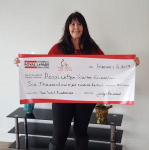 Sales representative Judy Larmand of Royal LePage In Touch Realty presents the proceeds of her Comedy Night fundraiser, held in support of the Royal LePage Shelter Foundation.
