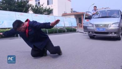 صورة صيني يسير بحذاء وزنه 300 كيلو جرام ويسحب سيارة برقبته!