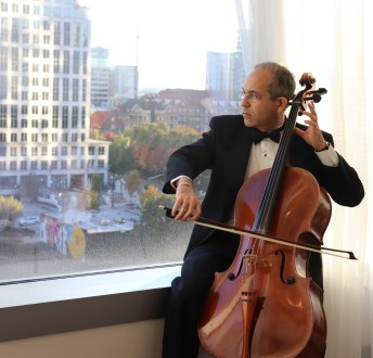 Cellist Roy Harran prepares before performance.
