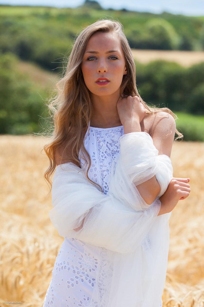 Mathilde en robe blanche et voile dans un champs de blé sur Lanildut