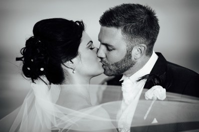Black and white wedding photography of bride and groom kissing