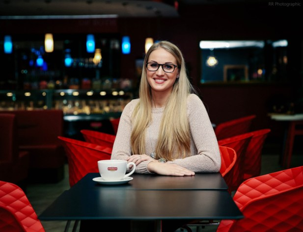 Ruta sat at a black table and smiling at the camera in Sprinkles, Winton