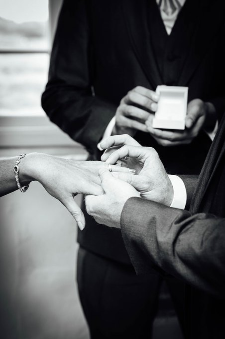 Groom putting the wedding ring on his bride's finger