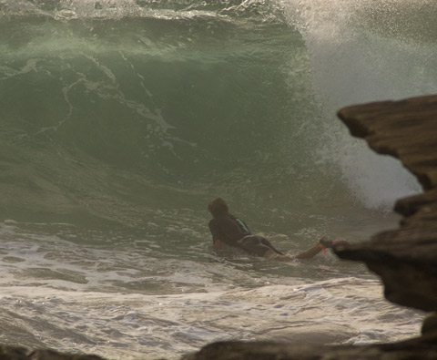 Bodyboarders hang in the impact zone in front of the rocks at South Curl Curl