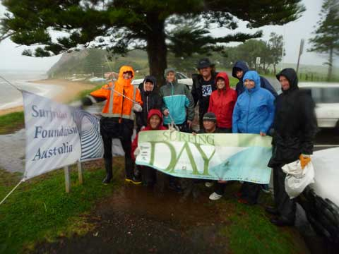 Rain lashing in as we posed for a snap to mark International Surfing Day.