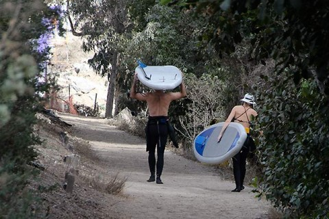 Hauling their paddleboards down for a 2-person sesh at the point
