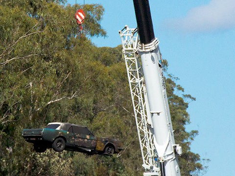 Vintage mustang being lifted away from burnt out car carrier south of Kempsey